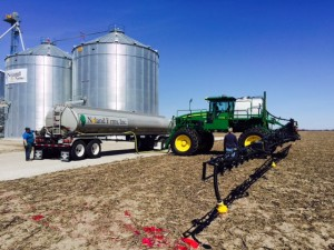 Andrew and Jeremy loading a fertilizer/chemical mix into the sprayer for corn.