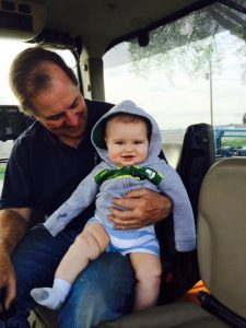 Duane taking grandson Harrison on his first ride planting corn.