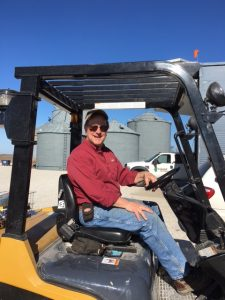 Duane operating a forklift while loading corn into the seed tender.